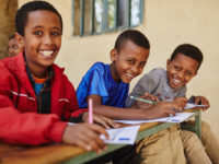Three boys sit in a row at a desk outside, each writing a letter. They all smile at the camera.