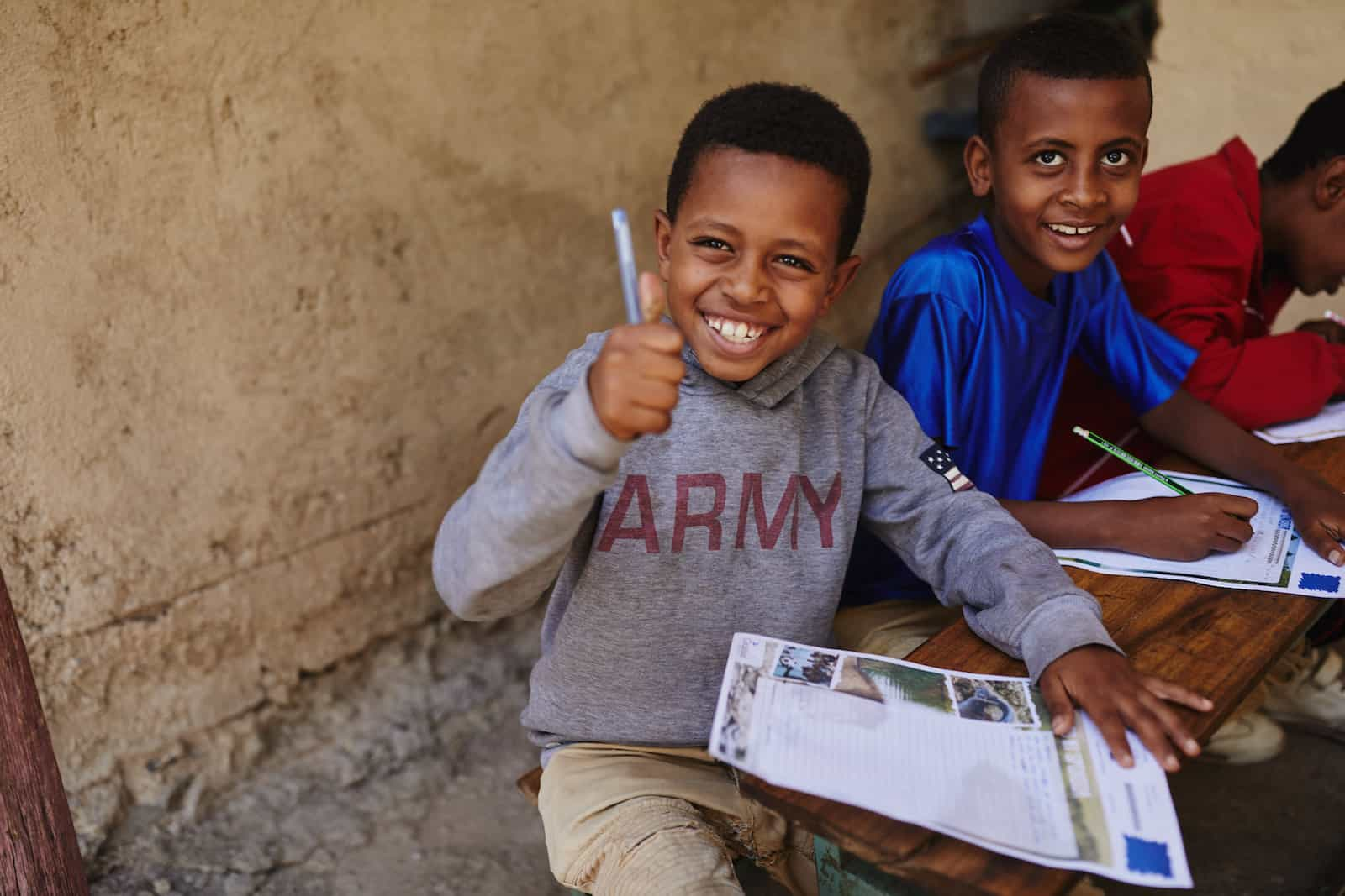 "A boy wearing a grey sweatshirt that says ""Army"" gives the thumbs up sign while holding a pen and paper."