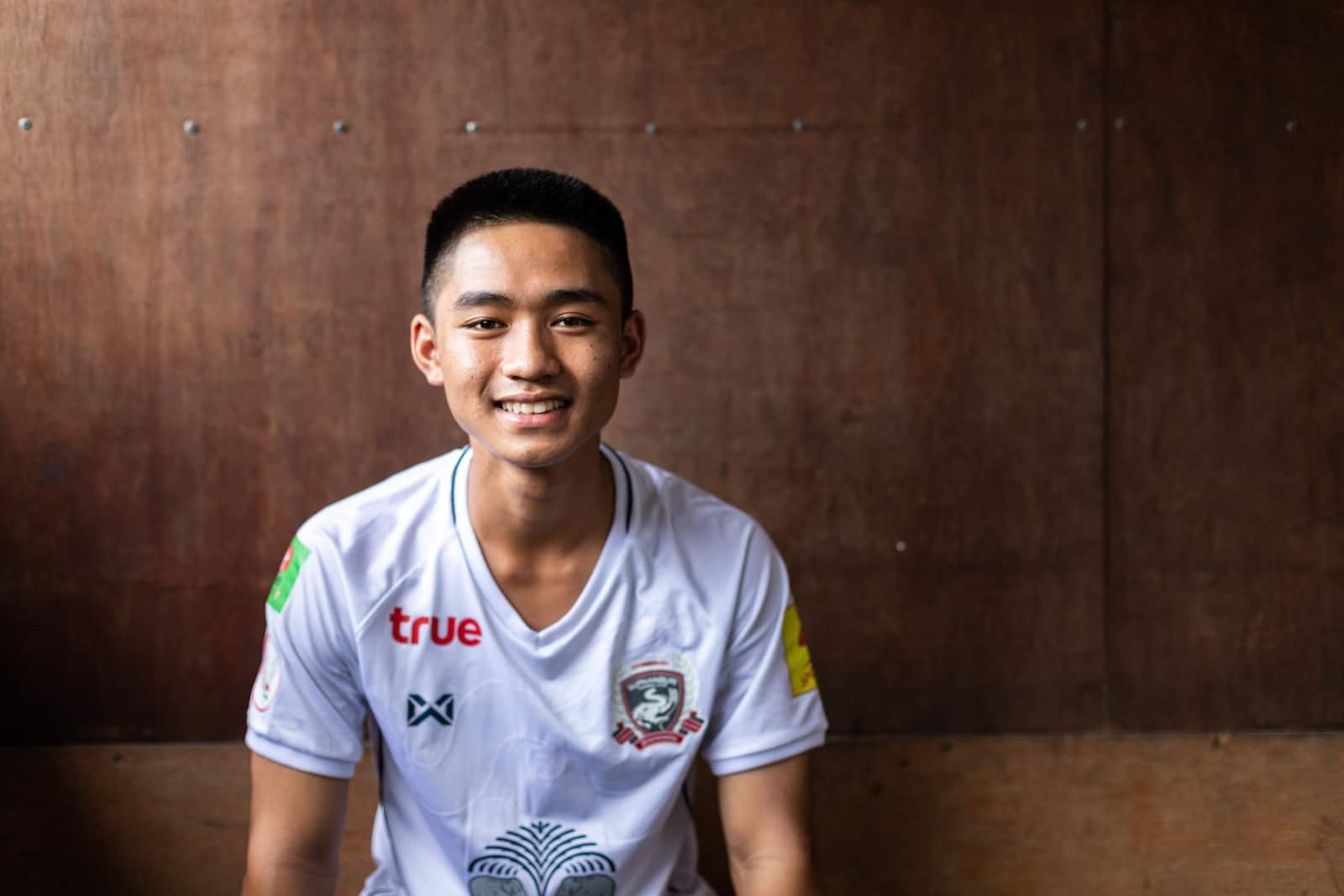 A teenage boy wearing a white T-shirt sits in front of a brown background and smiles at the camera.