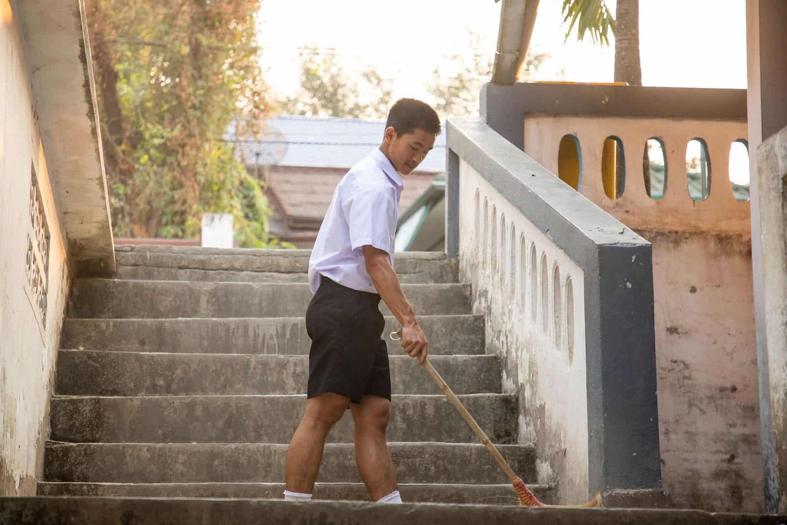 A boy sweeps the stairs outside at a concrete building with trees in the background.