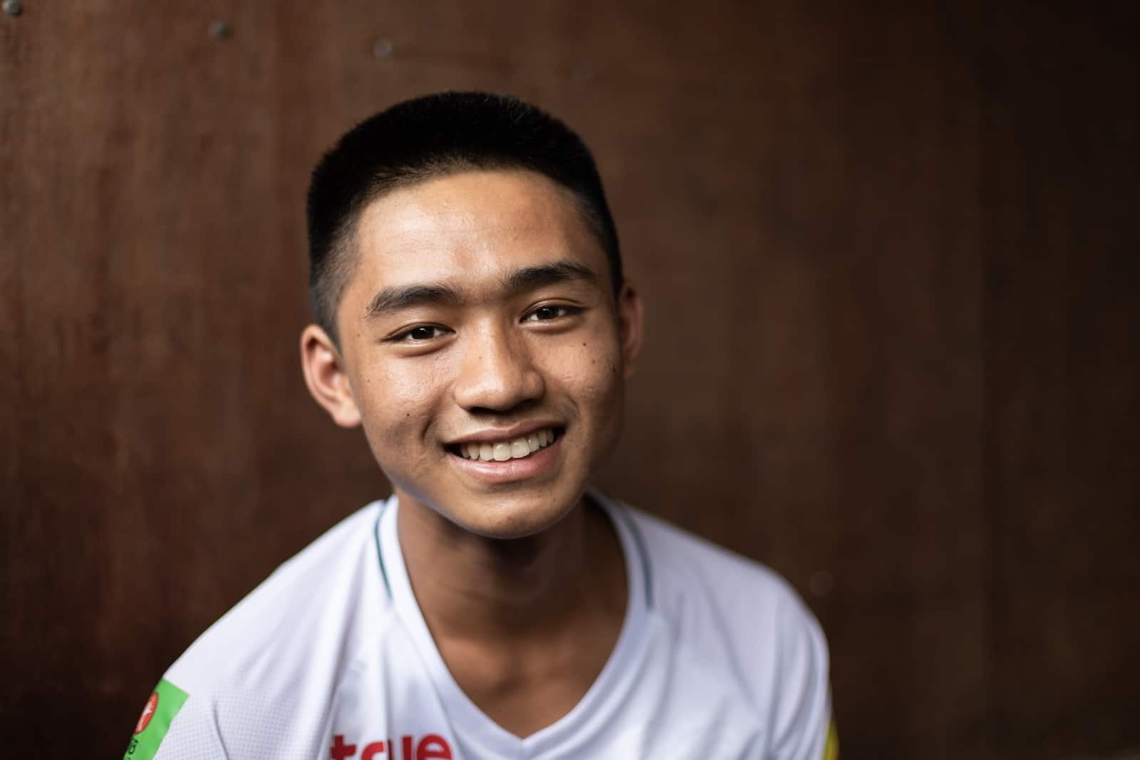 A teenage boy, Adun who was part of the Thailand cave rescue, wears a white shirt smiles at the camera. He sits in front of a brown background.