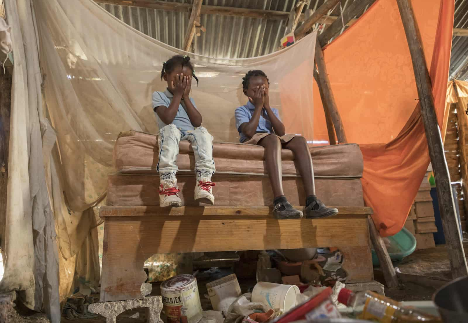 Two girls sit on a bed with their faces covered in prayer. The bed is raised up with concrete blocks. A mosquito net hangs above the bed and the roof is made from corrugated metal.