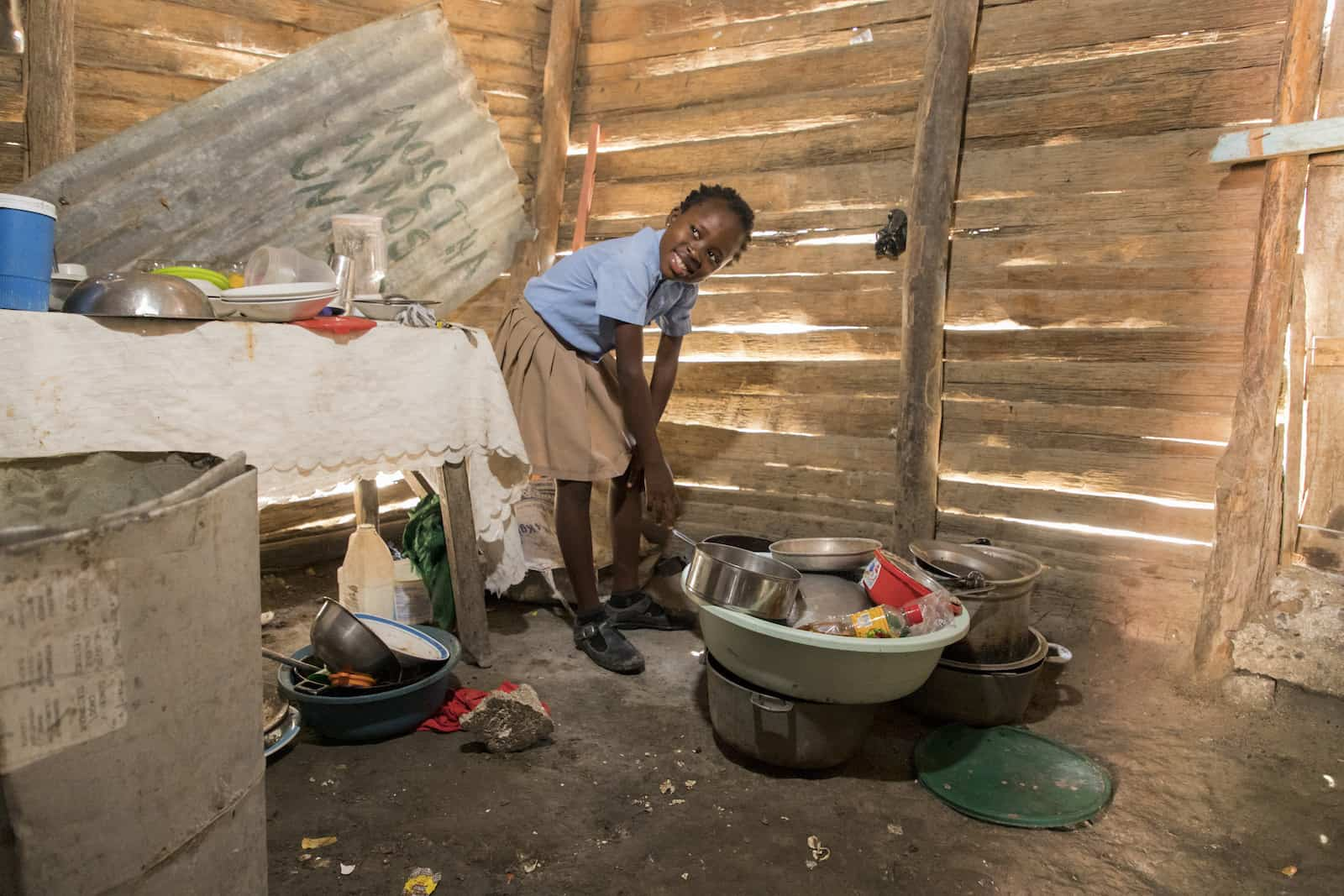 A girl in a blue shirt and tan skirt leans over pots and pans on a dirt floor. There is a table to one side. The walls are made of wood slats with holes in them.