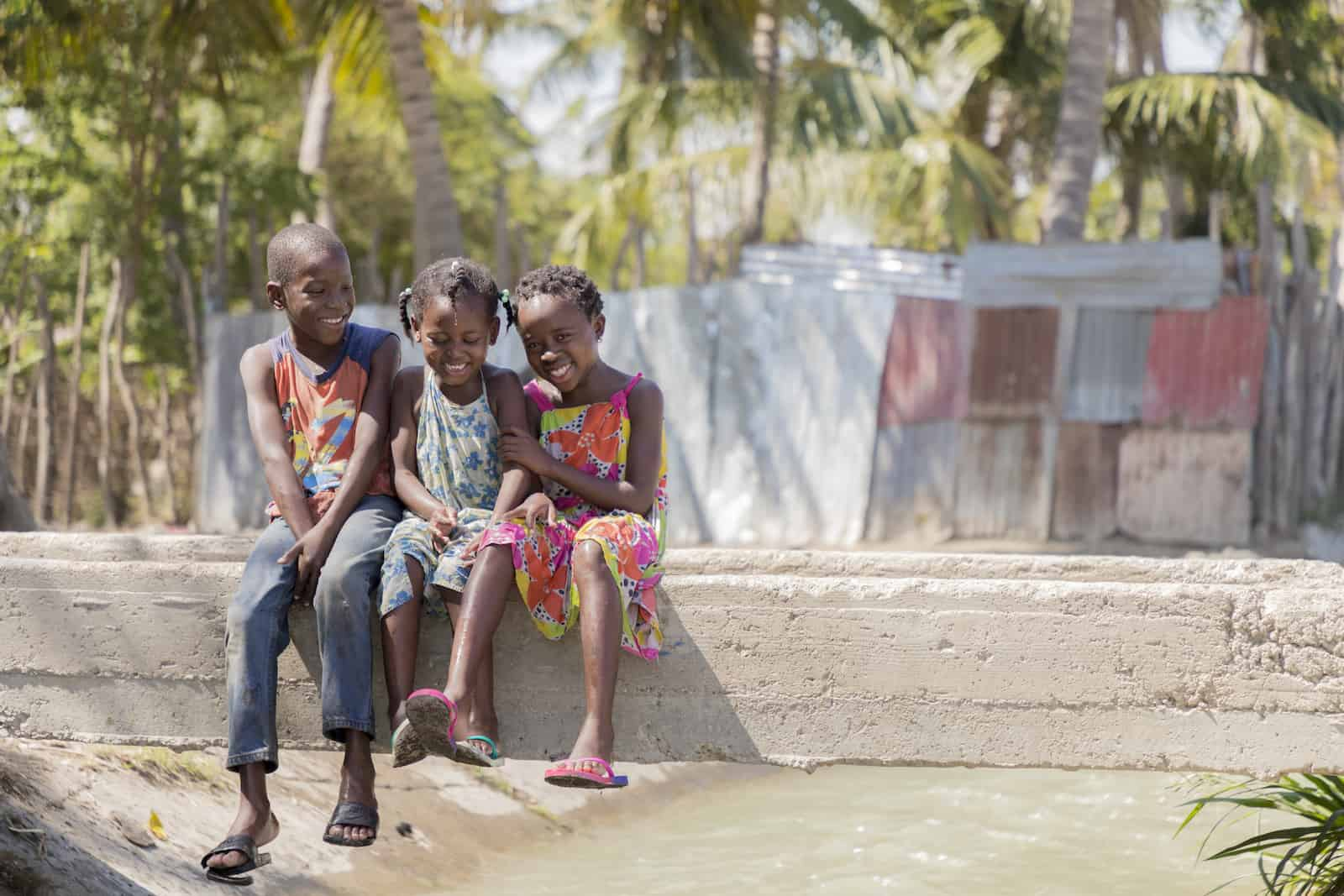 Three young children sit on a concrete beam that is a bridge across a ditch full of water. In the background are palm trees and corrugated metal sheet homes.