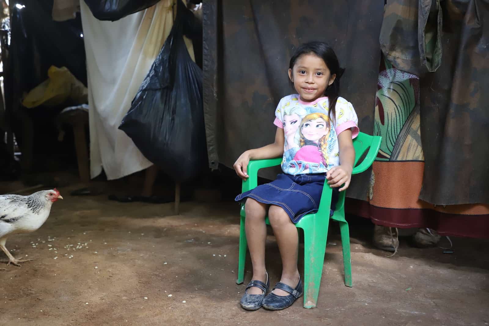 "A girl in an ""Anna and Elsa"" shirt and jean skirt sits in a green plastic chair inside her home in Central America. There are large plastic tarps hanging from the ceiling to serve as walls. A chicken eats corn on the floor."