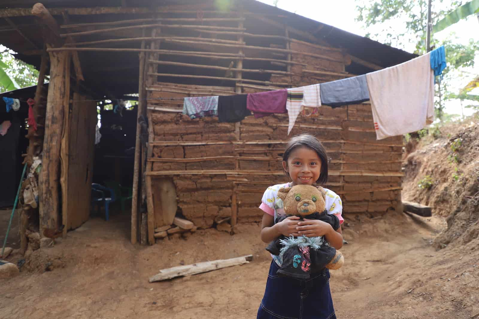 A girl holds a teddy bear, standing in front of a home in Central America made with mud and sticks. There are many holes in the walls. A laundry line hangs out front.