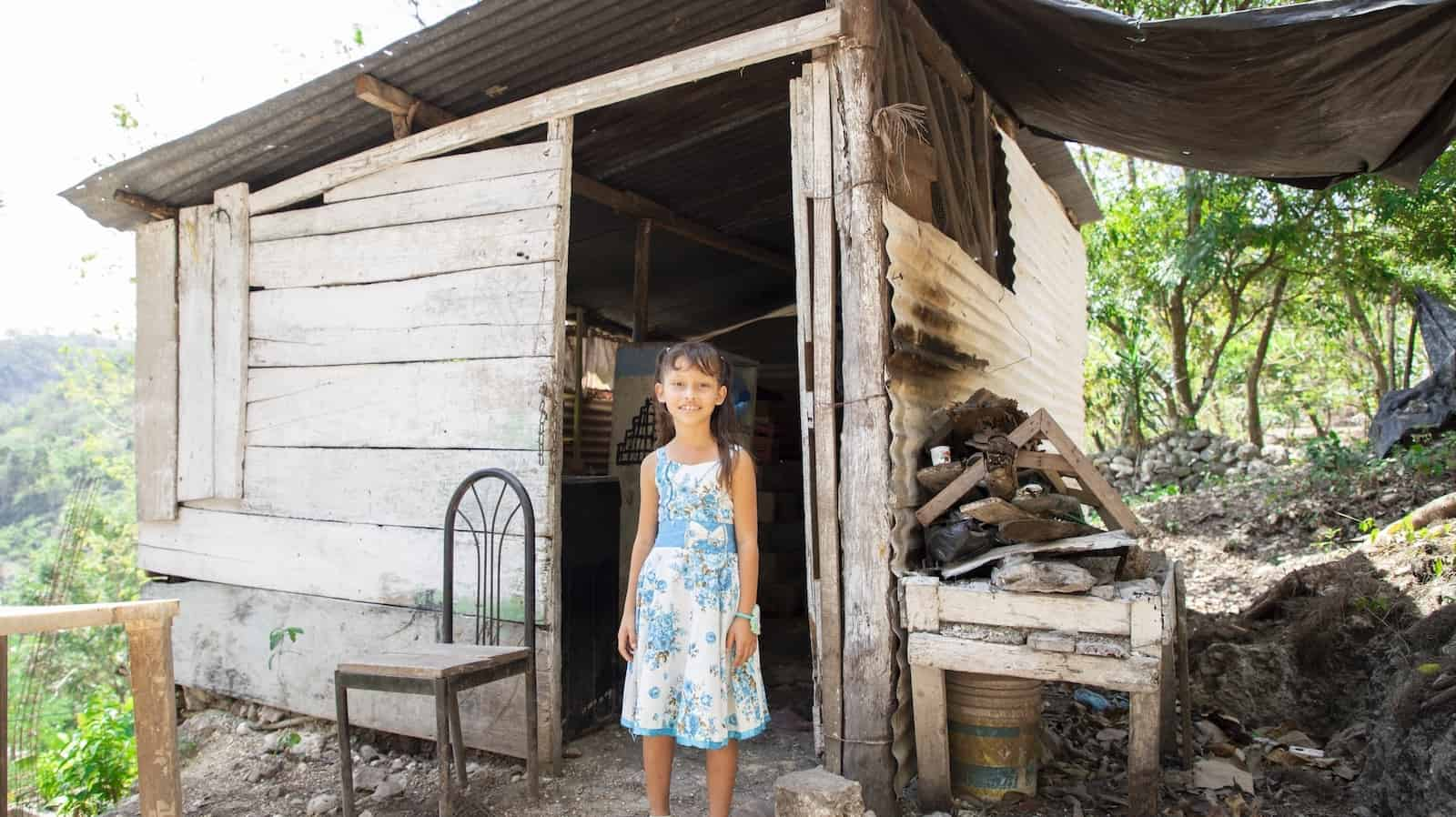 A girl in a white and blue dress stands in front of a small home in Central America made from wood and metal sheets. In the background are green hills and tress.