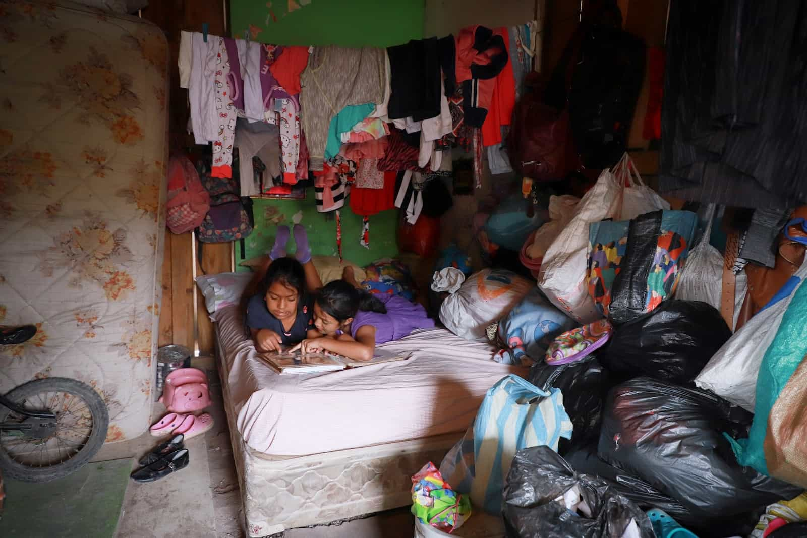 Two girls lie in a bed in a corner of a room, reading a Bible. A drying line of clothing hangs from teh ceiling and the walls and floors are covered in plasticbags, used for storage.