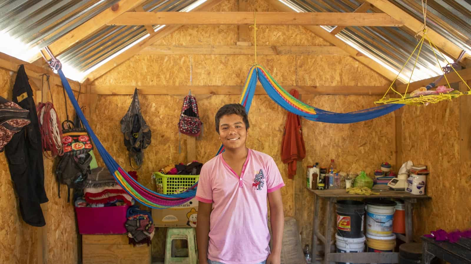 A boy in a pink shirt and jean short stands in the interior of a home built from plywood and metal sheets. Colorful hammocks hang from the ceiling, and personal items, like backpacks hang on the walls. There is a small table in one corner.