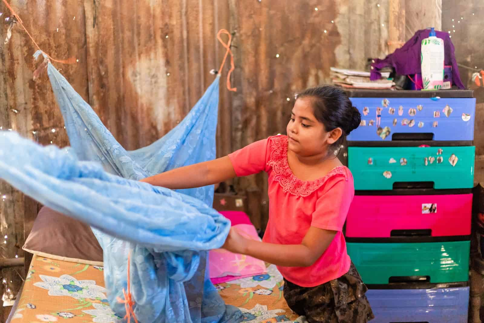 A girl in a pink shirt adjusts a mosquito net above a bed. There is a brightly colored plastic dresser in the background, in front of worn corrugated metal walls.