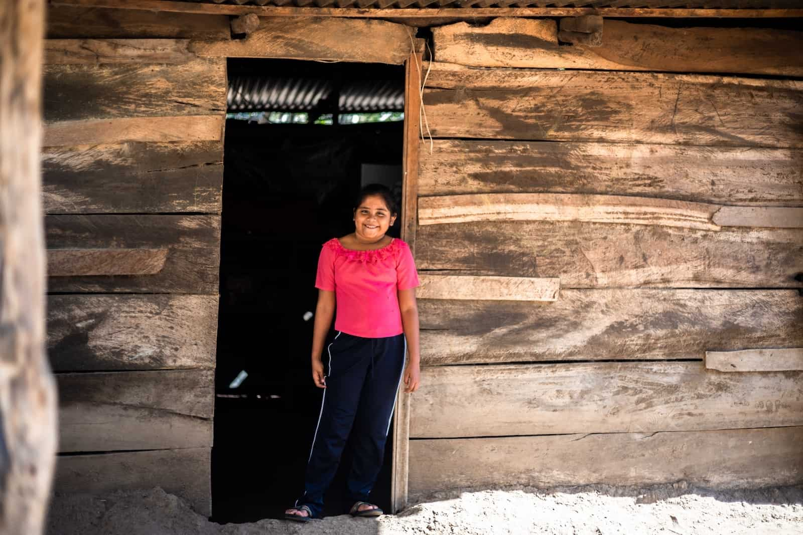 A girl in a pink shirt and jeans stands in the doorway of a wooden home in Central America.