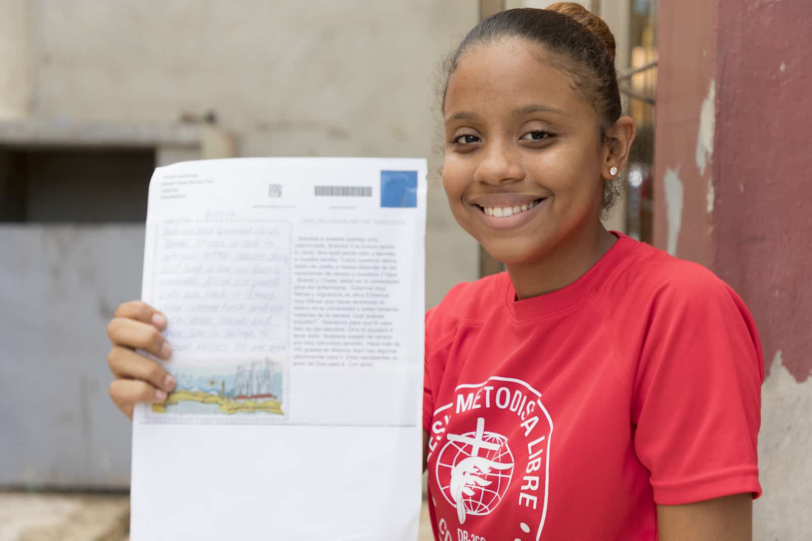 A girl in a red T-shirt smiles and holds up a letter. She sits in front of a concrete wall and wooden post.