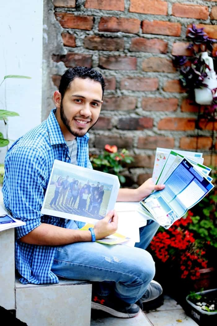 A young man wearing a blue shirt and jeans sits, holding letters and photos, smiling at the camera. In the background is a brick wall and flowers in a pot.