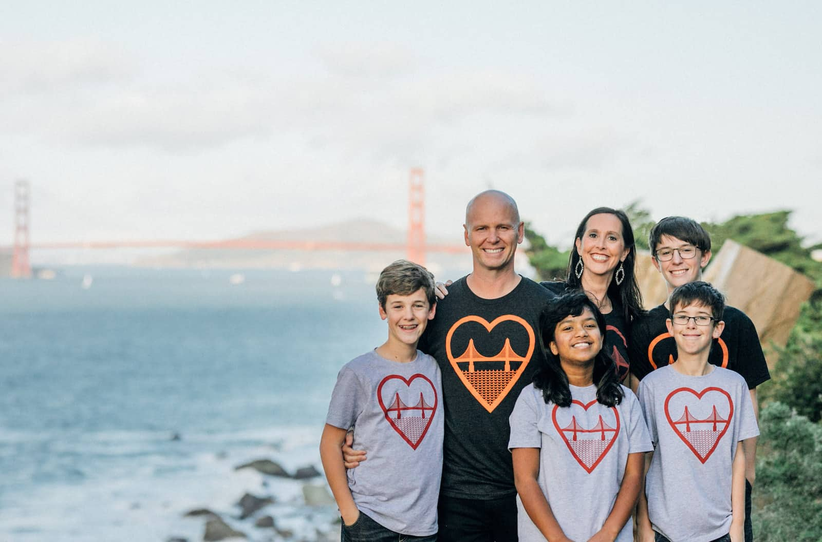 A man and woman and four children stand in front of the Golden Gate Bridge, wearing T-shirts with a graphic of the Golden Gate Bridge on it.