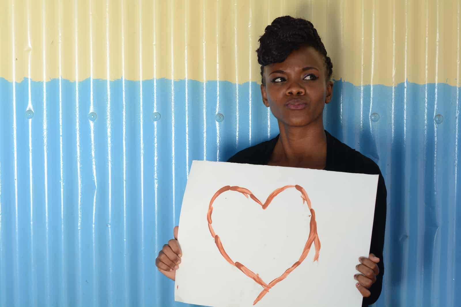 A young woman leans against a blue and white corrugated metal wall holding a white sign with a heart drawn on it.
