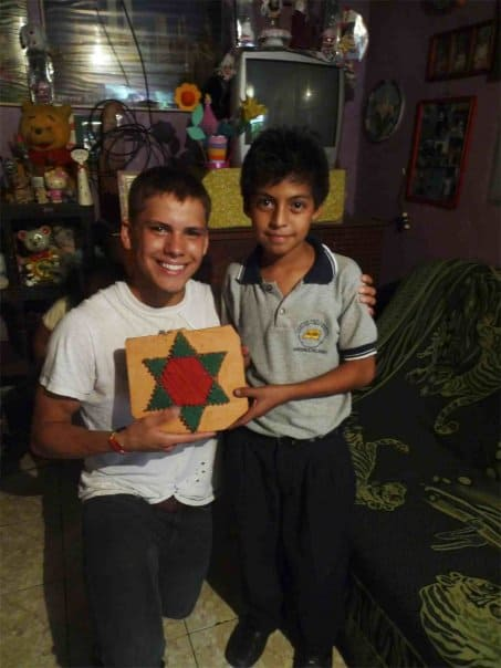 A teenage boy kneels net to a boy as they hold a pillow with a star on it together. They are inside a dark home.
