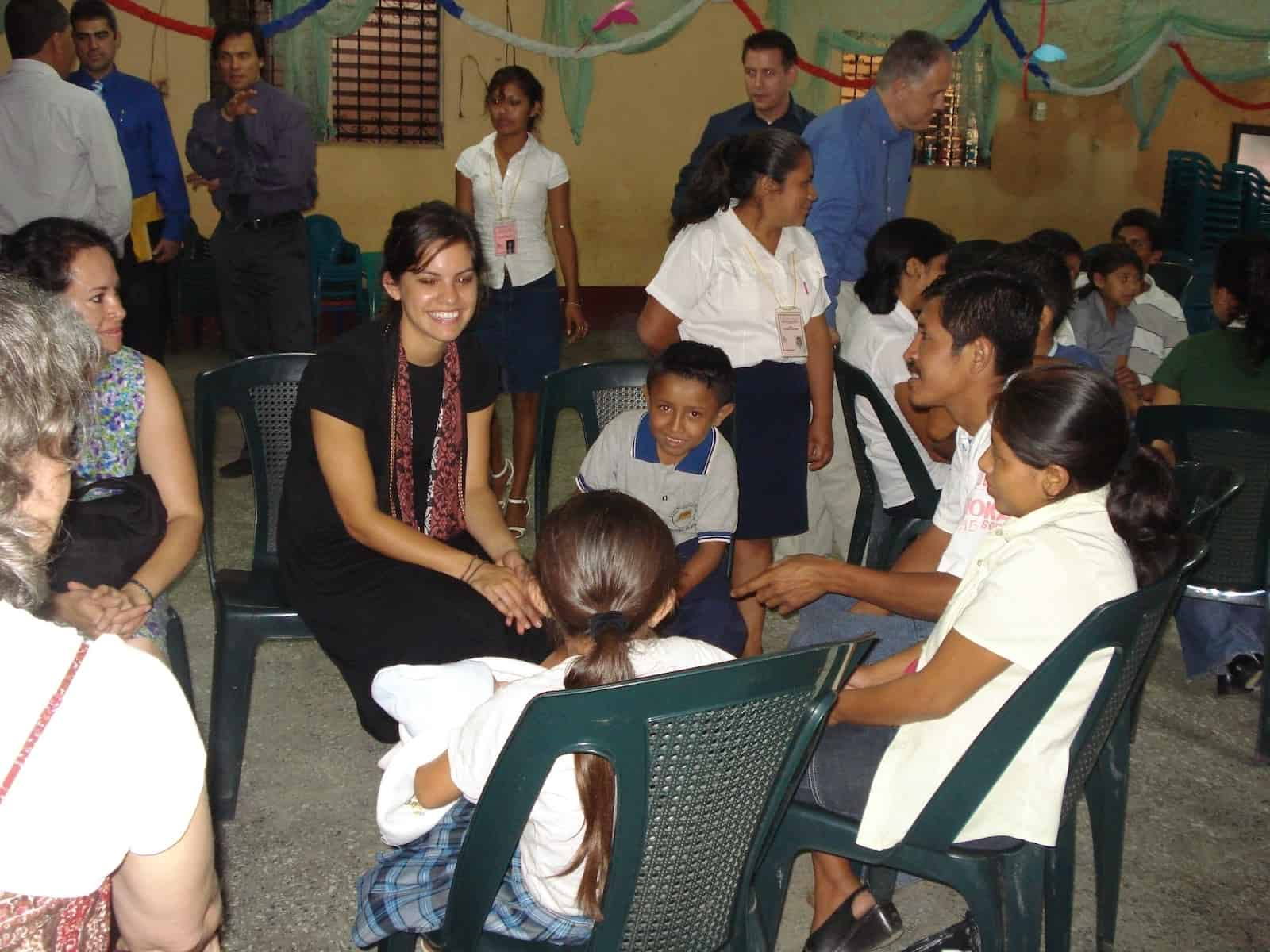 A girl sits in a circle of chairs, talking to children inside a church room.