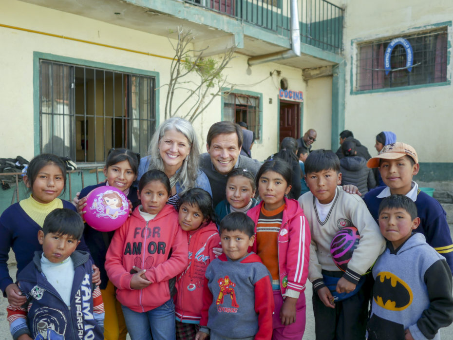 Two people, Jimmy and Leanne Mellado, pose for a group photo with a group of children in Bolivia.