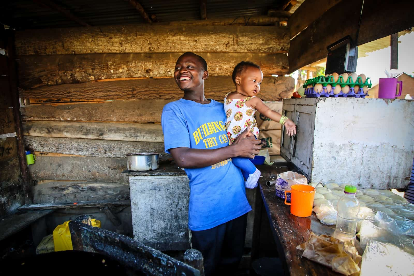 A man wearing a blue T-shirt holds a baby girl in his arms, standing in an open-air kitchen with breads and eggs on a table.
