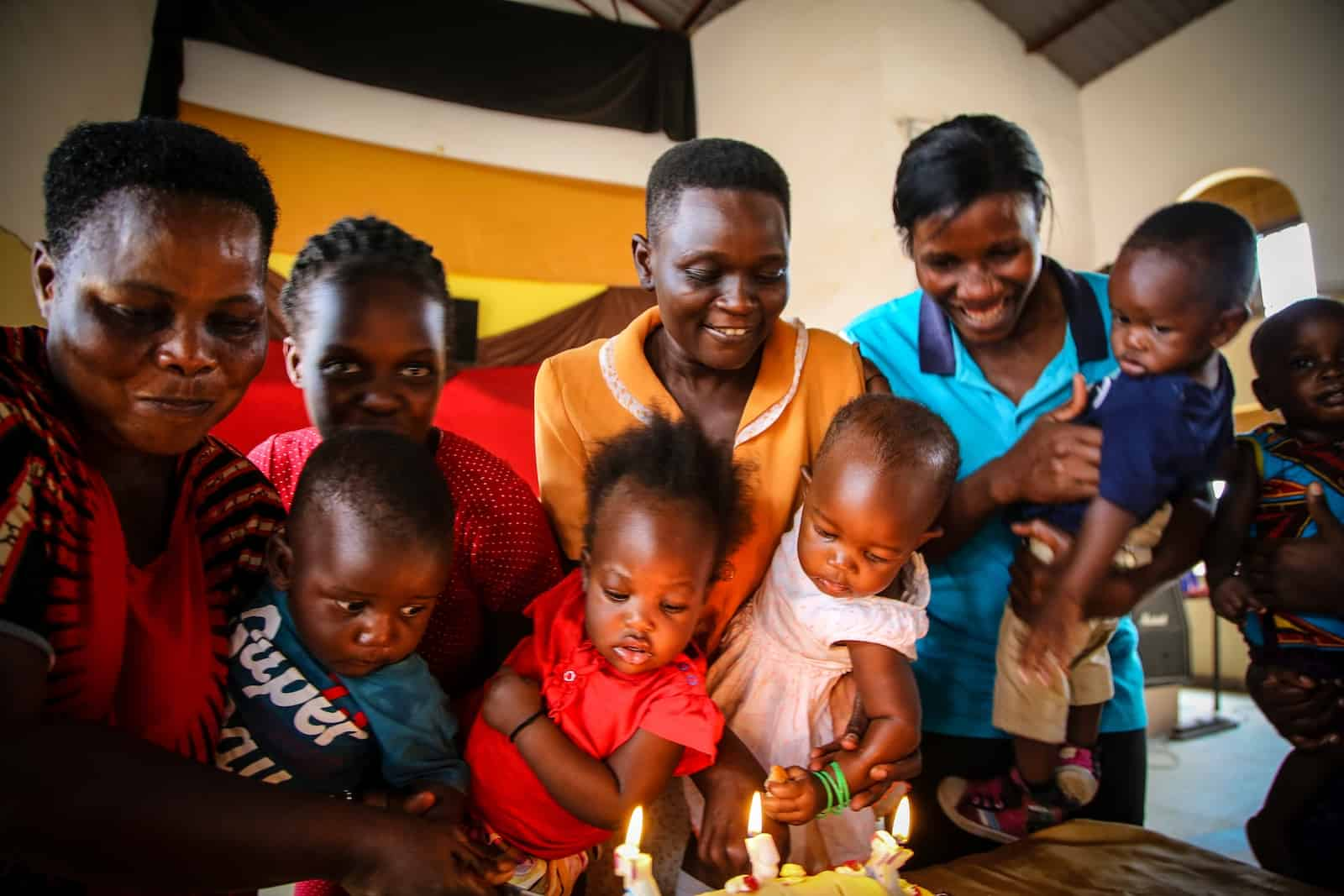 A group of woman holding babies leans over a cake with candles lit. Everyone is looking at the cake.