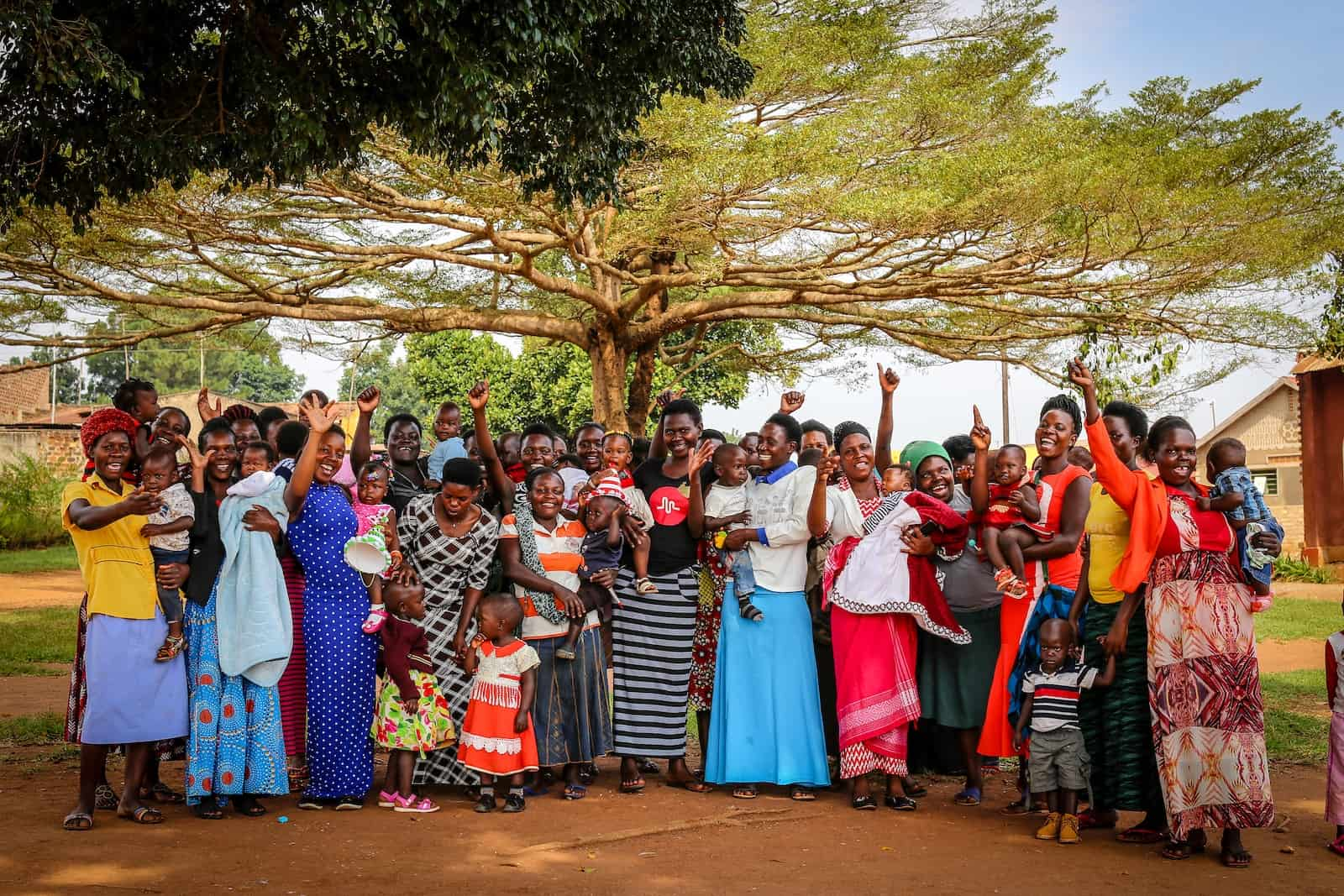 A group of women wearing long dresses and holding babies stands under a tree and cheer, some raising their hands in the air, celebrating an important birthday milestone.