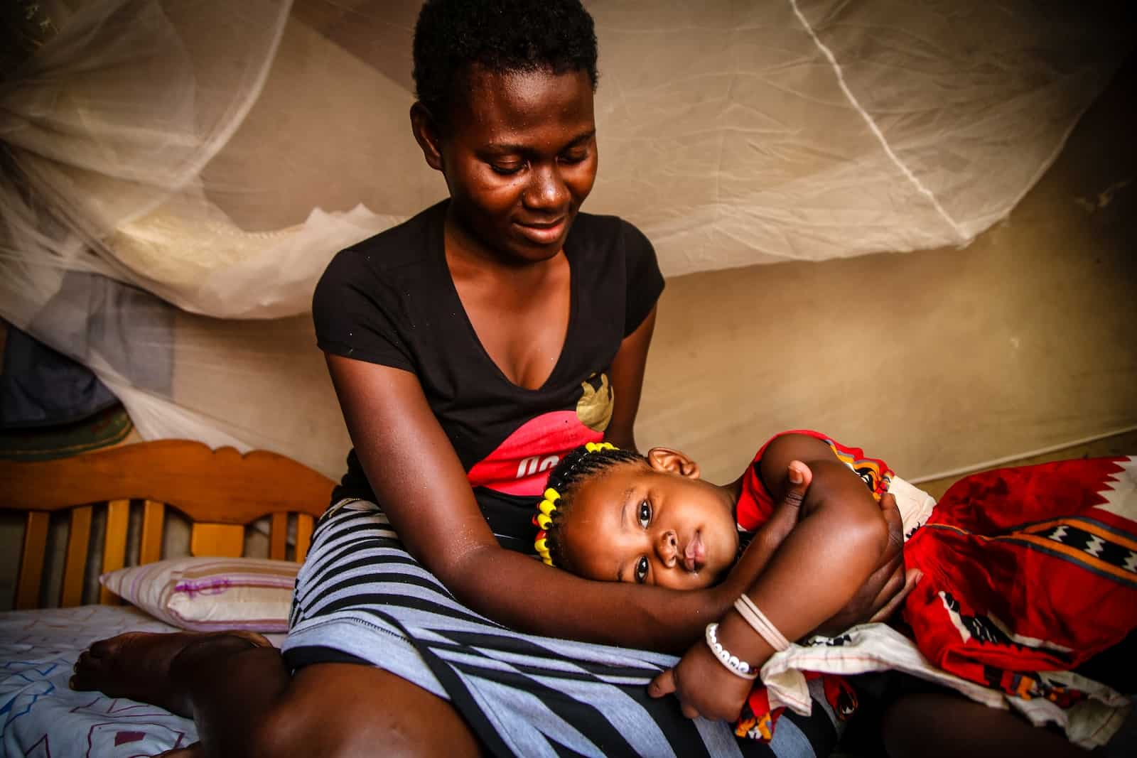 A girl wearing a red and white dress lays on her mother's lap. The mom wears a black shirt and black and white striped dress. They sit on a bed with a mosquito net on it.