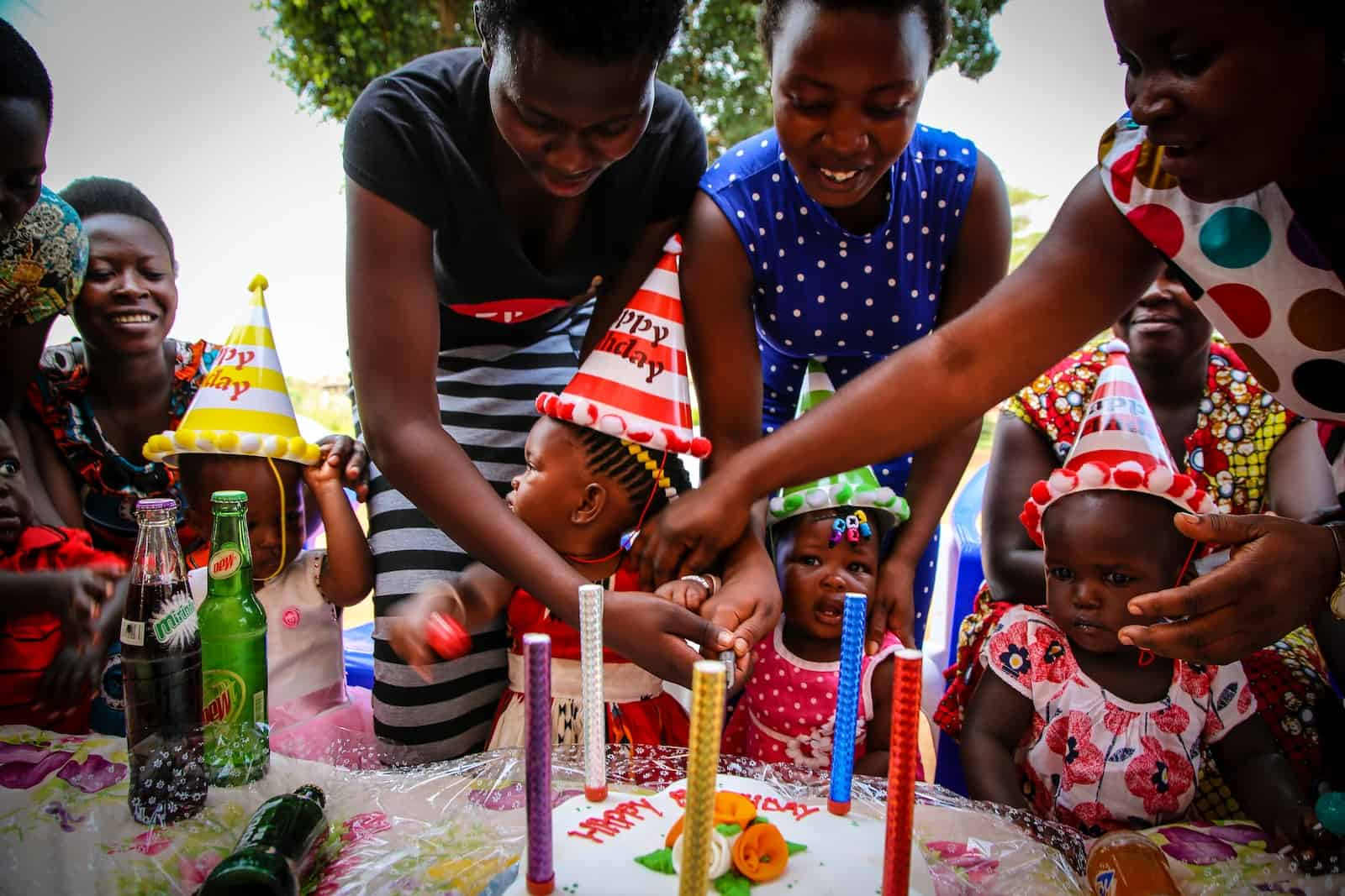 Three babies sit at a table with a cake in front of them to celebrate a birthday milestone. They are wearing party hats and women stand behind them, helping them.