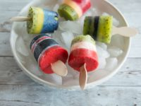 A white bowl full of ice holds five multi-colored popsicles, on a gray table.