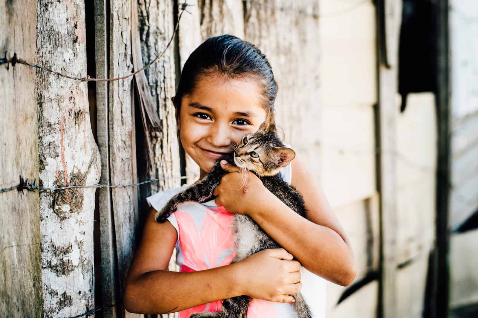 A young girl wearing a white T-shirt cuddles a kitten in front of a wooden fence.