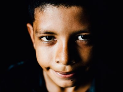A close-up of a young boy smiling at the camera in front of a black background.