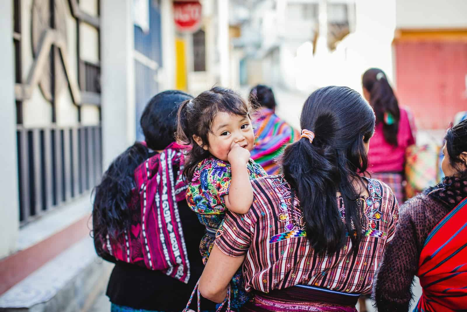 A baby is held by her mom, surrounded by other women walking down a street, wearing colorful clothing.