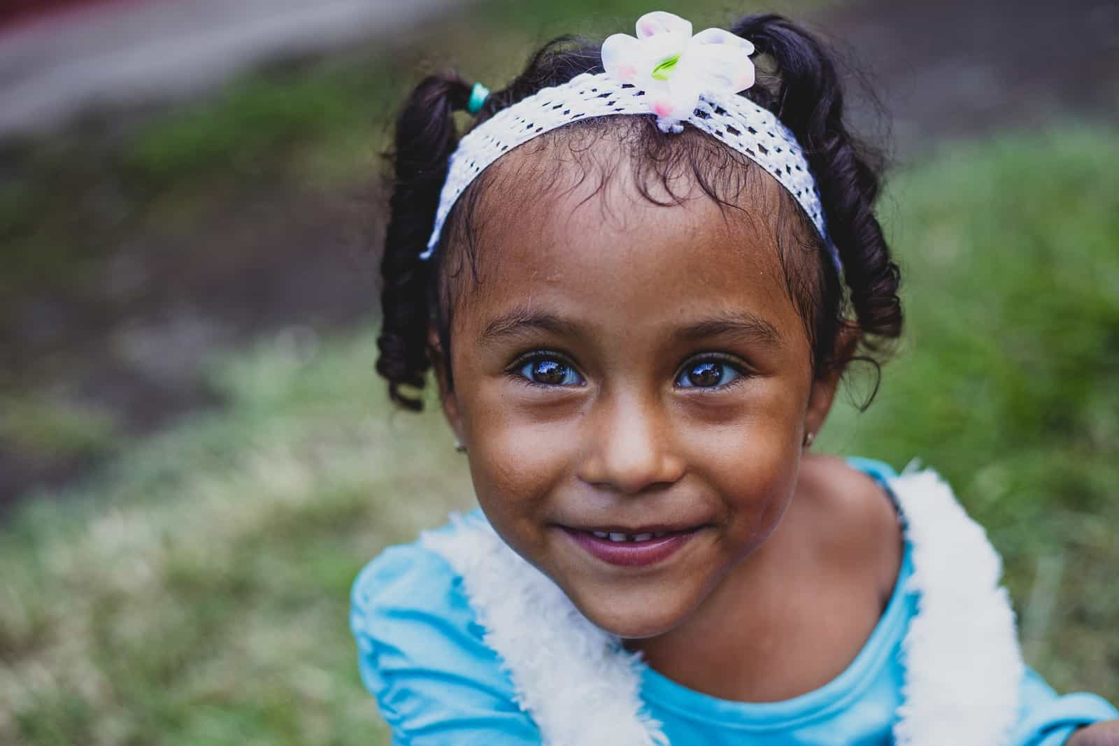 A girl in a blue shirt and white headband with a flower on it looks up into the camera.