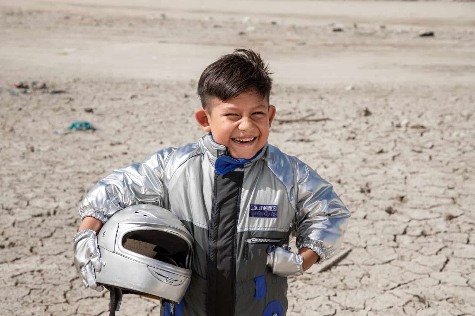 A boy wearing a silver suit and holding a silver helmet stands with one hand on his hip, smiling, in front of a dry, parched dirt background.