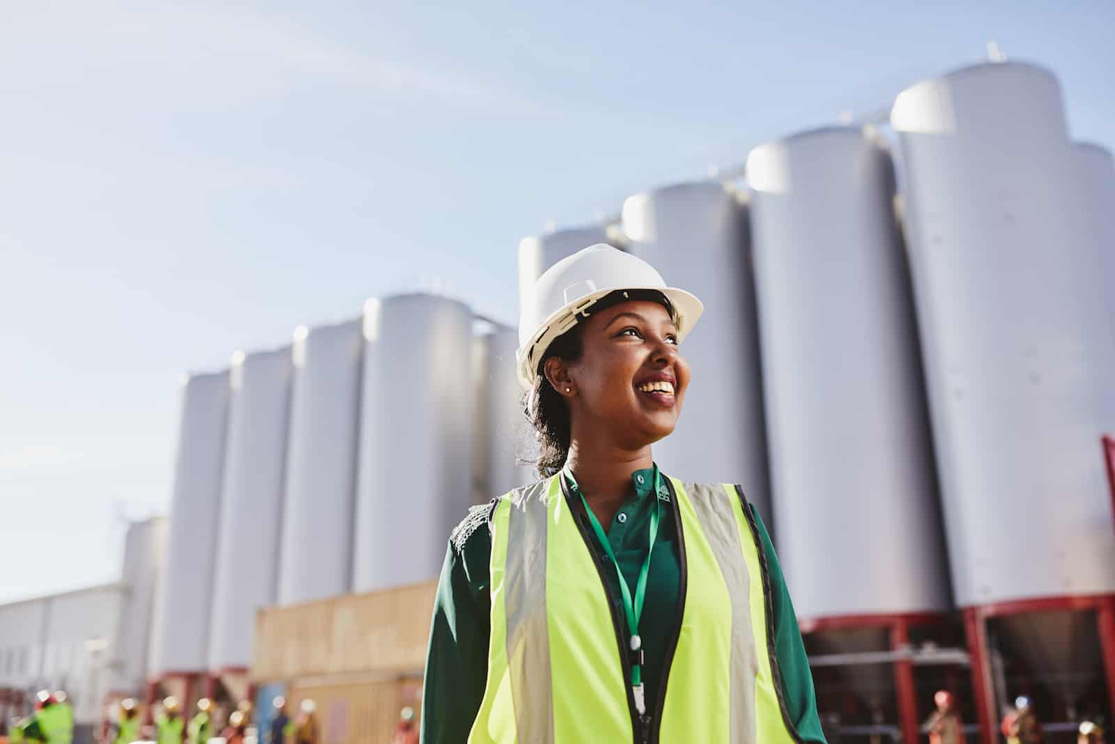 A woman in a yellow safety vest and hard hat stands in front of a manufacturing plant, looking up to the sky.