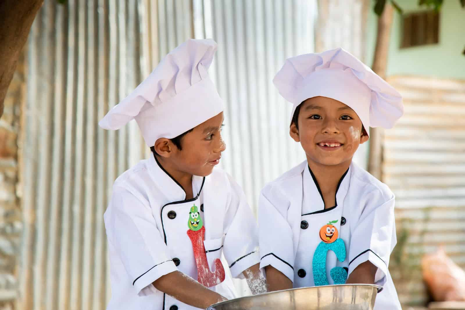 Two boys wearing chefs hats and white chefs jackets stand at a table, with their hands in a large silver bowl. One smiles at the camera and one looks at the other boy.