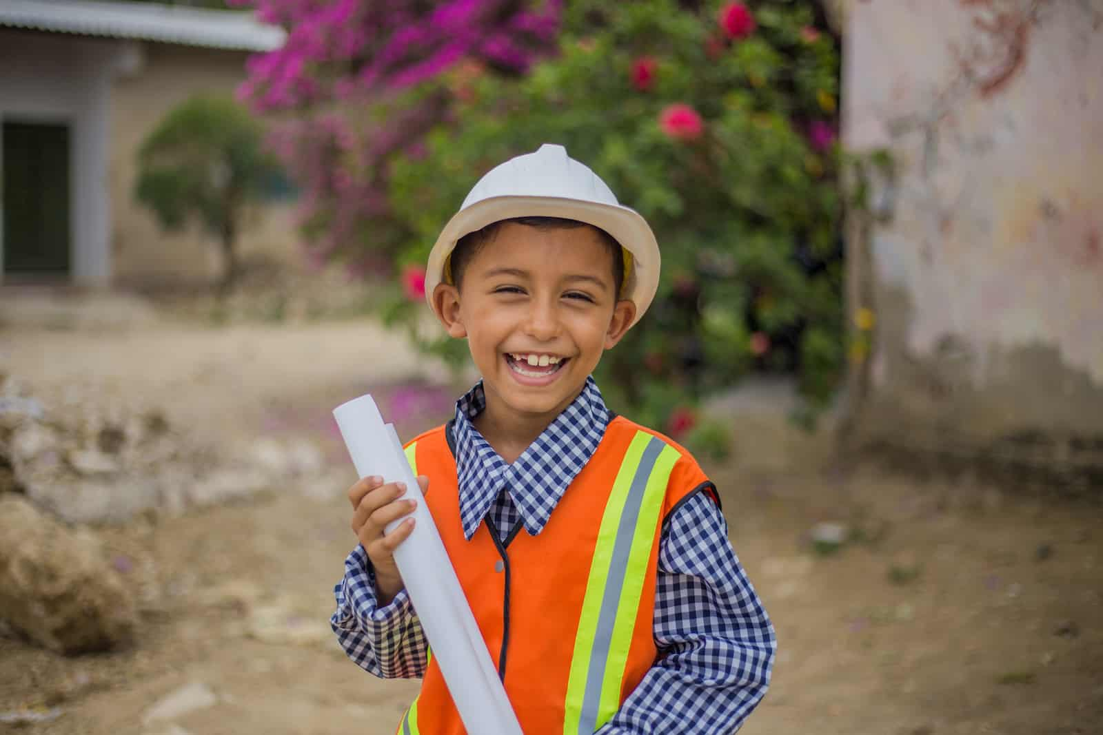 A boy wears a orange safety vest over a blue shirt, along with a hard hat. He holds a rolled up piece of paper, smiling at the camera. He stands on a street in front of a bush with pink flowers.