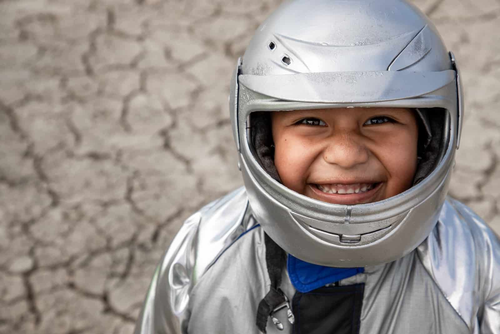 A boy wearing a silver helmet and silver astronaut suit smiles up at the camera. He stands in front of dry, parched ground.