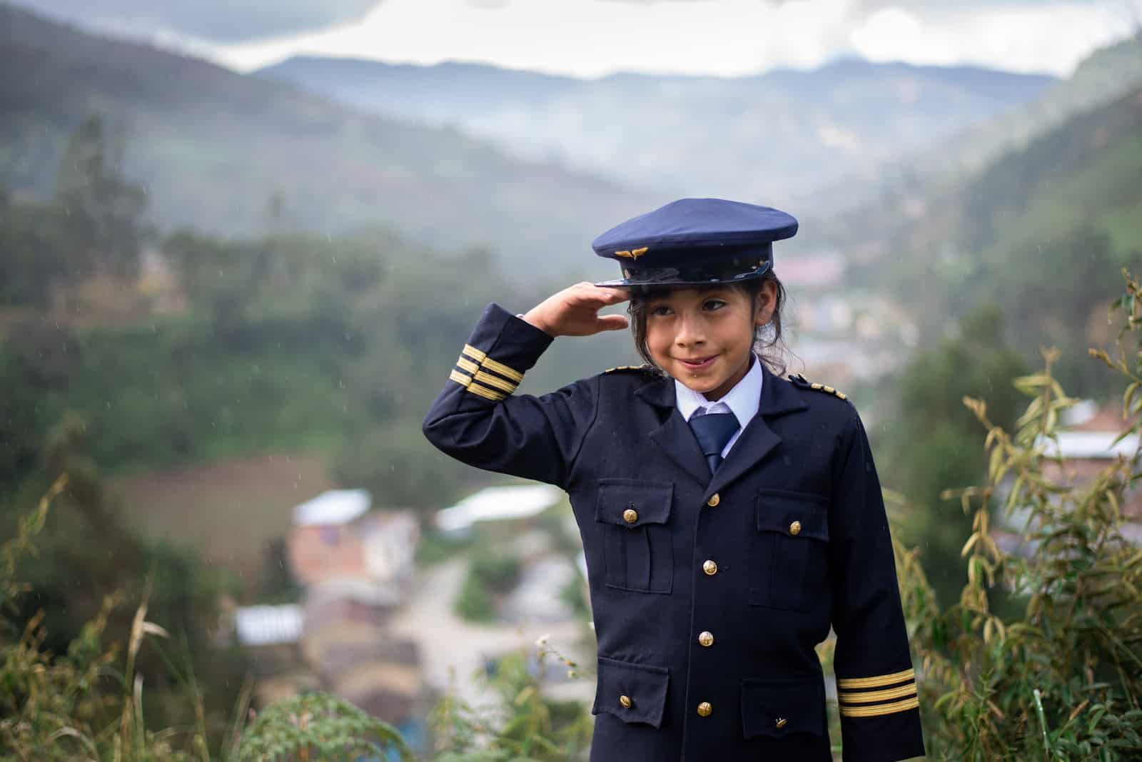 A girl in a blue pilot's uniform and hat salutes. Behind her is a village in a mountain valley.