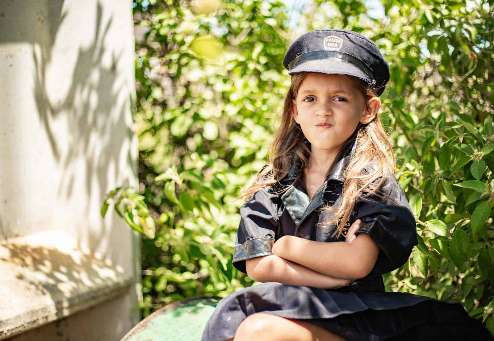 A young girl wearing a black police officer costume and cap crosses her arms in front of her, while sitting in front of a bush. Her lips are pursed in a funny face.