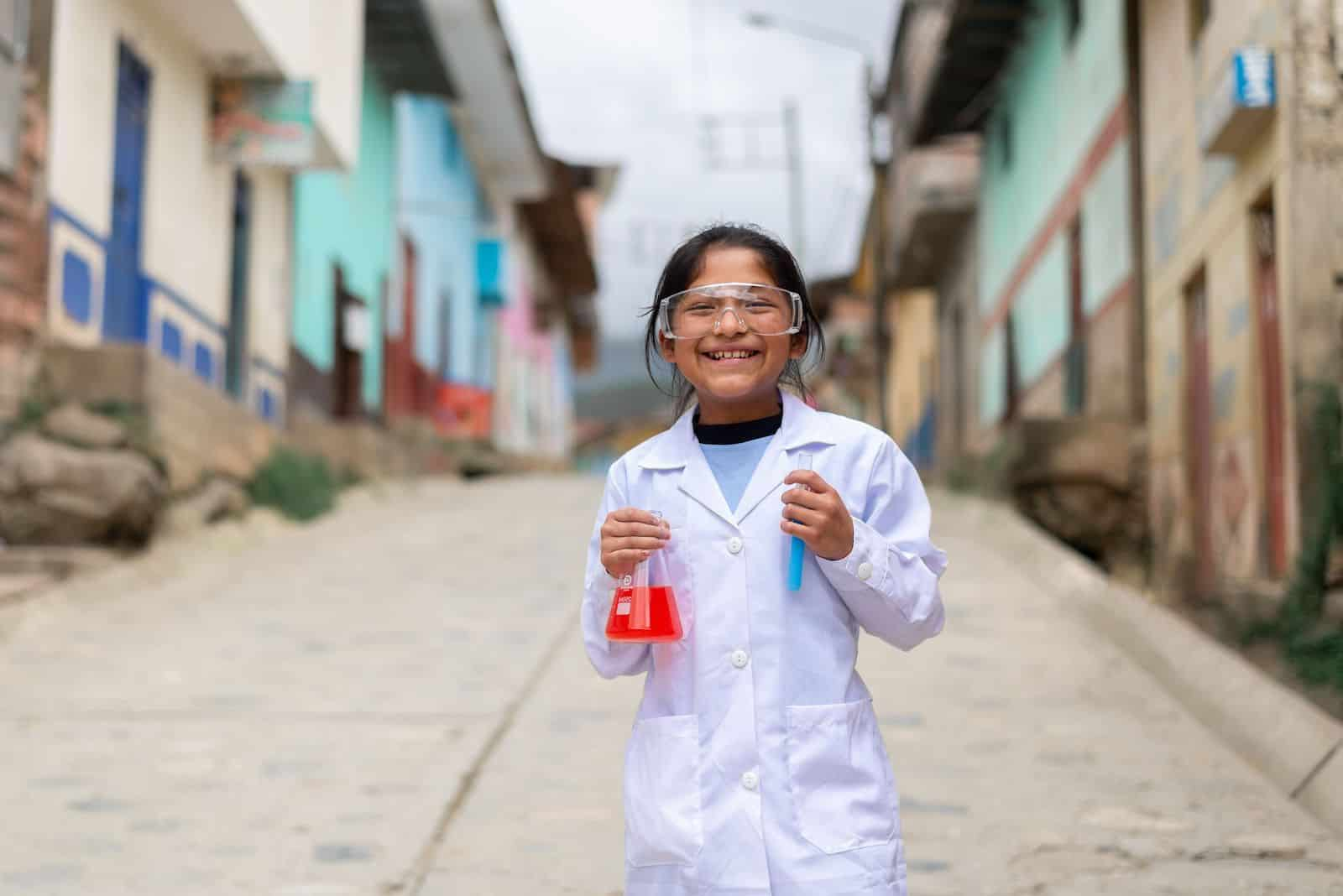 A girl wearing a white lab coat and safety glasses holds two beakers full of red and blue liquid, smiling at the camera. She stands on a street with a row of concrete homes.