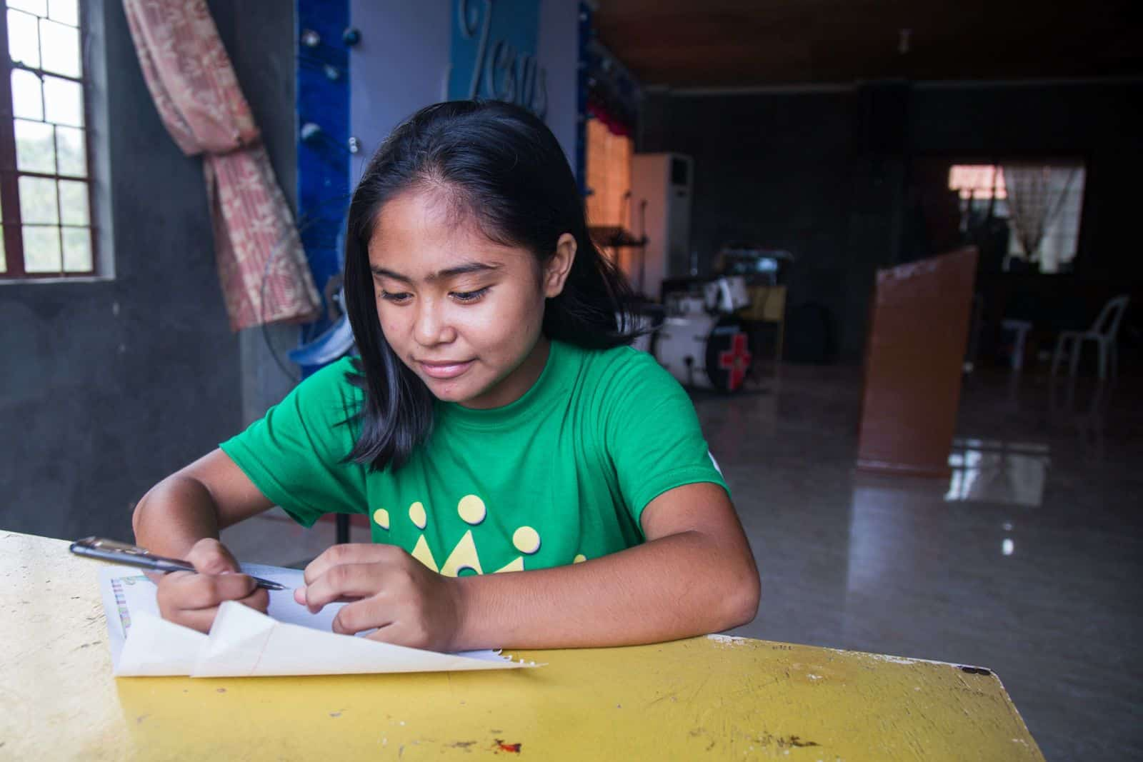 A girl in a green T-shirt sits at a table inside of a church, writing a letter.