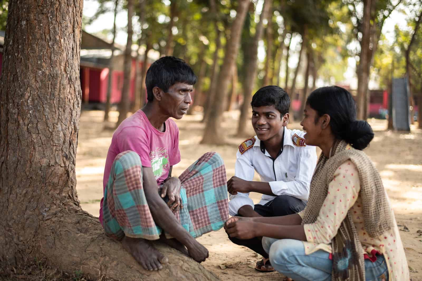 A man in a pink shirt and traditional plaid skirt kneels in front of a tree, faced by two smiling teenagers sitting on the ground.