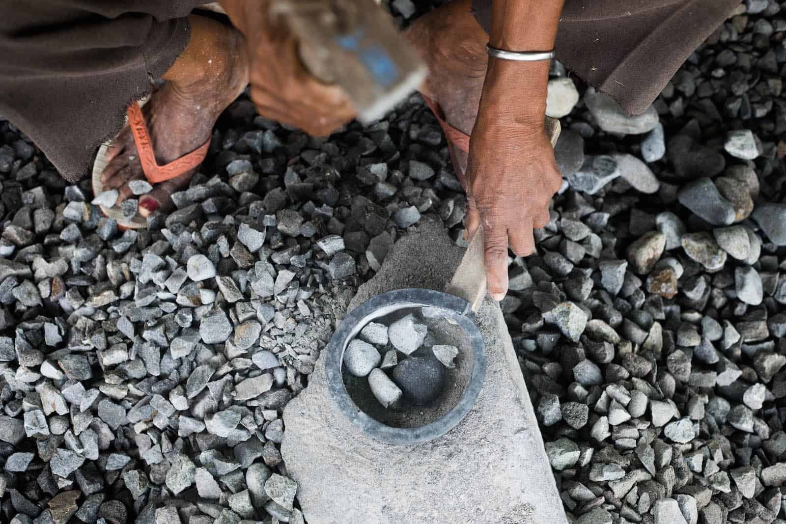 A hand holds a hammer, poised over a group of pebbles on a stone.