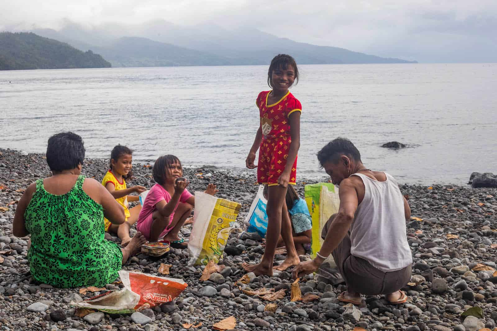 A girl stands on the beach, surrounded by girls and her grandparents collecting rocks.