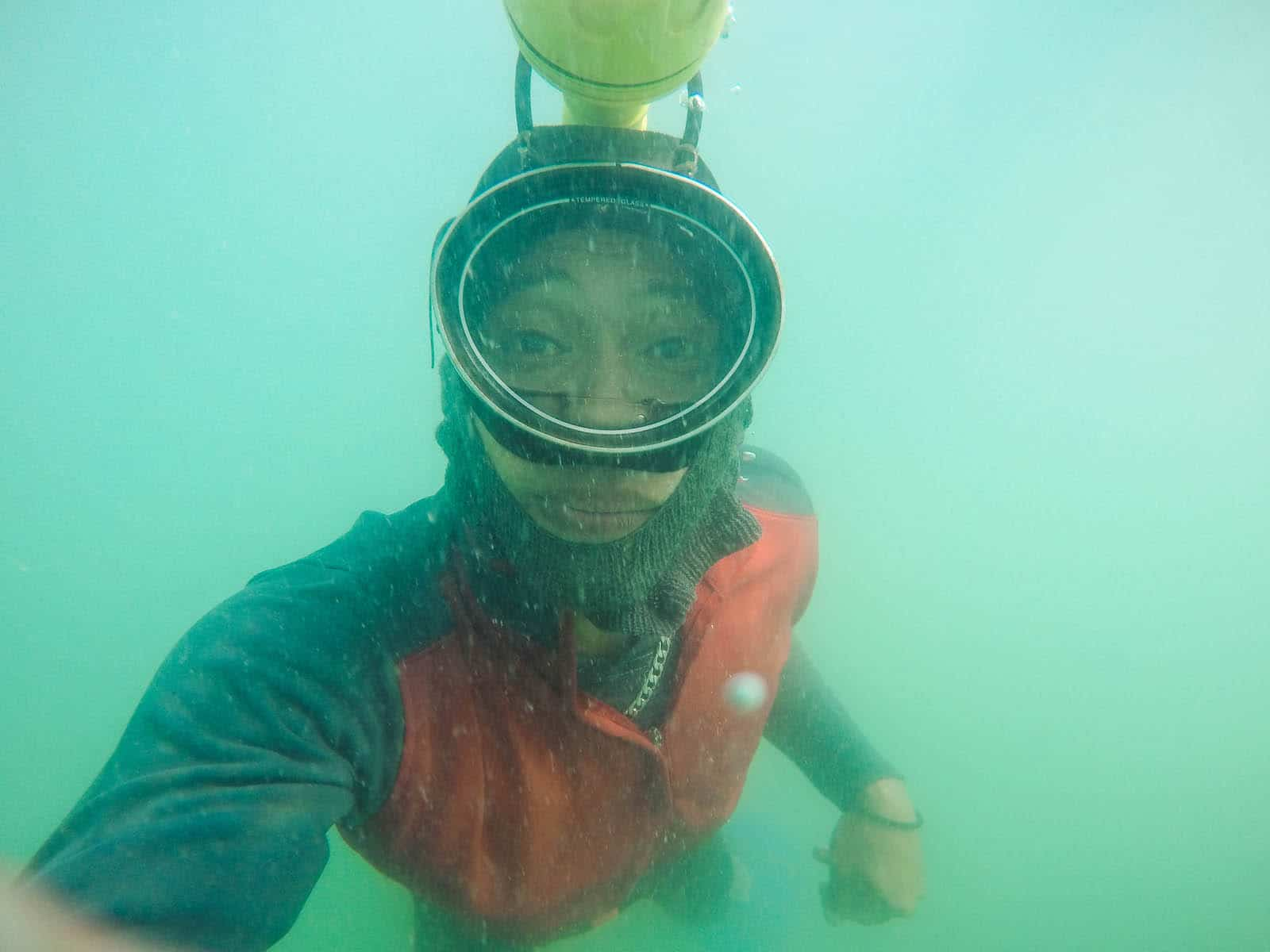 A man underwater, wearing a swim mask and a flashlight strapped to his head.