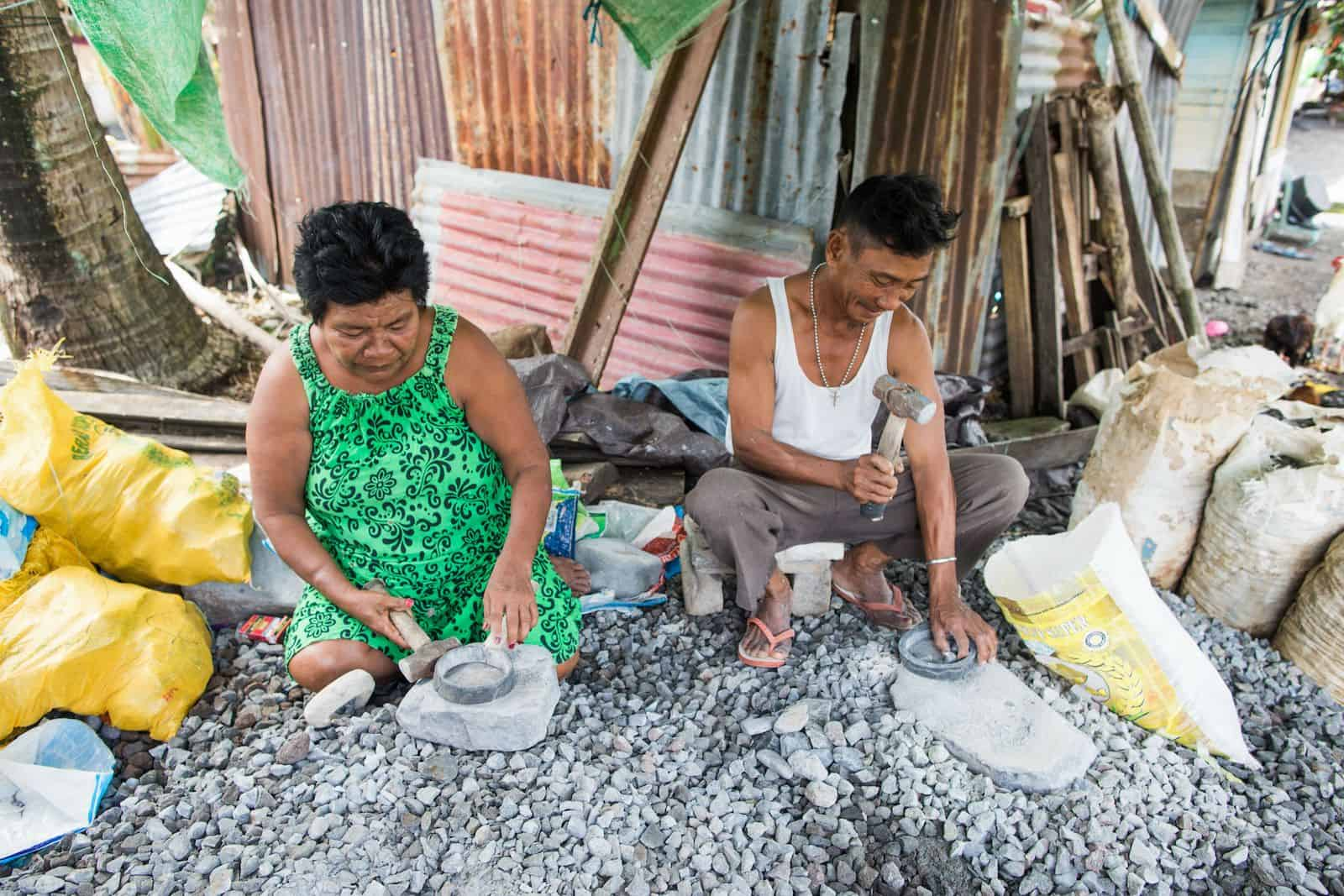 A man and woman crouch on the ground breaking rocks with small hammers.