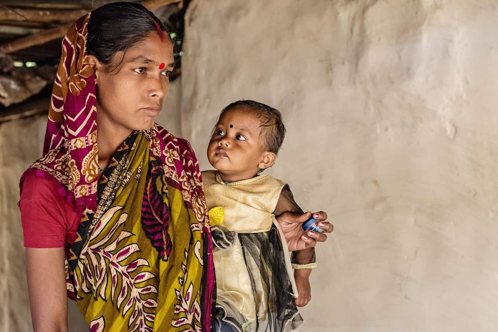 A woman in a colorful sari with a red bindi on her forehead holds a baby girl, who is looking at her. Report: Hunger Is on the Rise Around the World