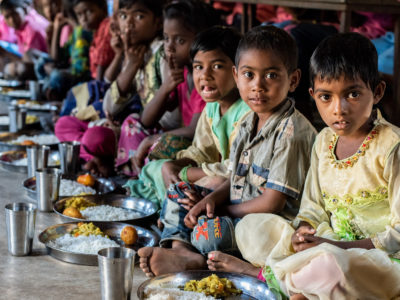A group of children sit on the floor in a line, eating plates of rice. Report: Hunger Is on the Rise in the World