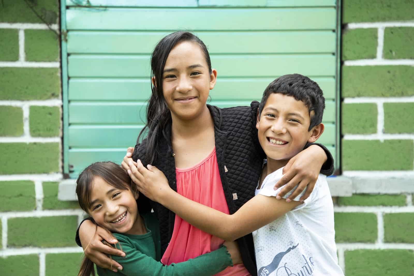 International Day of Friendship: Three children hug each other, standing in front of a green wall.