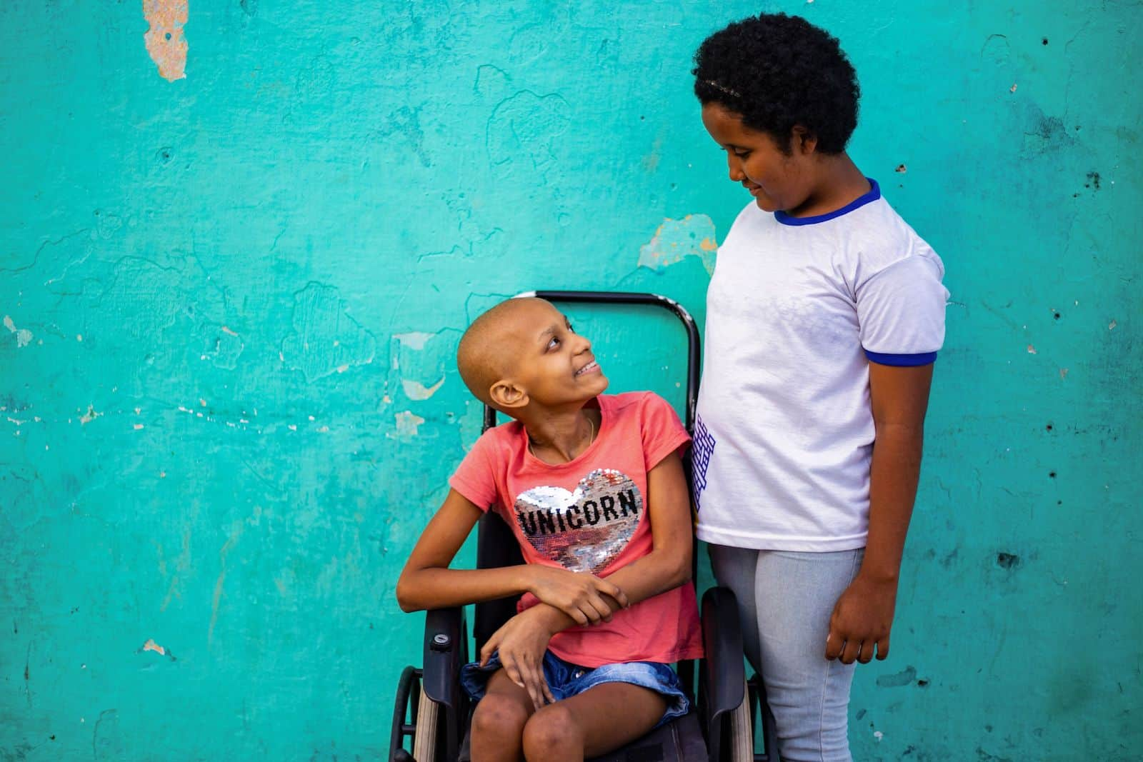 A girl in a white T-shirt stands next to a girl in a pink shirt, sitting in a wheelchair. They are looking at each other in front of a turquoise wall.